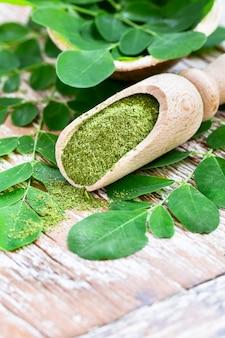 Moringapoeder in houten lepel met originele verse moringa-bladeren op houten lijstclose-up.