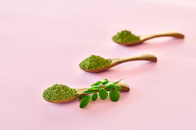 Moringapoeder (moringa oleifera) in houten lepels op roze achtergrond.