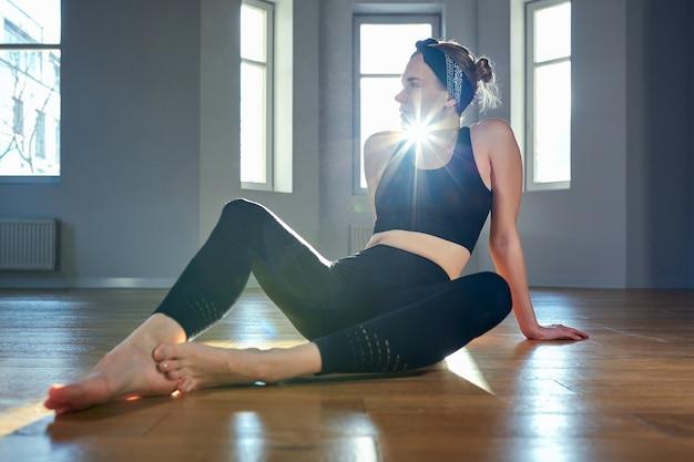 Morning yoga meisje doet rekoefeningen in de kamer voor pilates