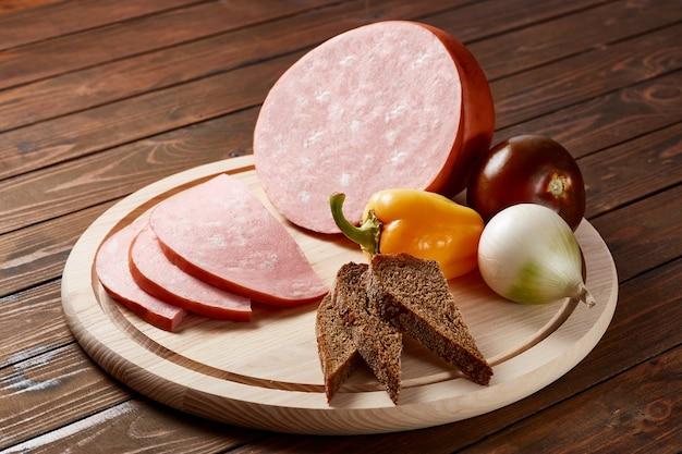Mortadella met groenten en kruiden op een houten plaat op een houten tafel.