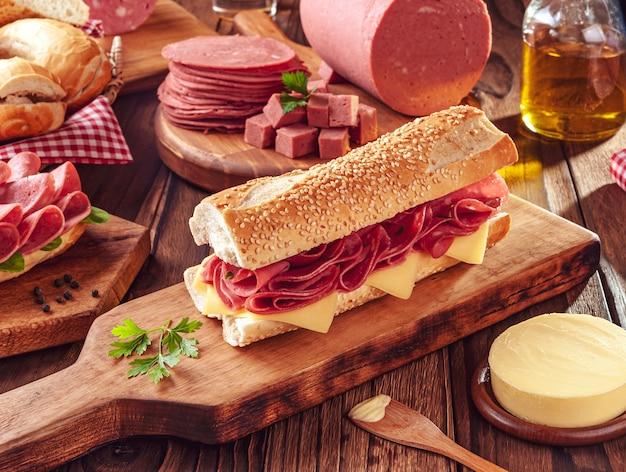 Mortadella sandwich met boter, brood en kruiden op houten snijplank