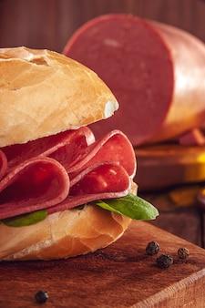 Mortadella sandwich met rucola en zwarte peper op houten snijplank
