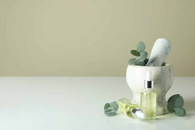 Mortel met eucalyptus en druppelflesjes olie op witte tafel