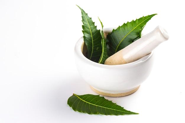 Mortier en een stamper met geneeskrachtige neembladeren op wit oppervlak