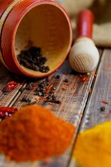 Mortier en een stamper met peper, chili in de buurt van kruiden op de houten tafel. hoop van verschillende droge kruiden op een houten achtergrond. detailopname.