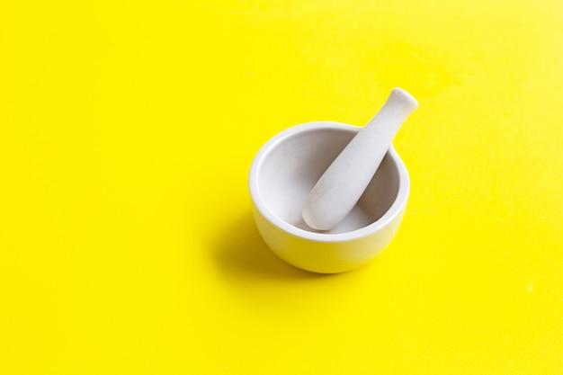 Mortier en stamper op geel.