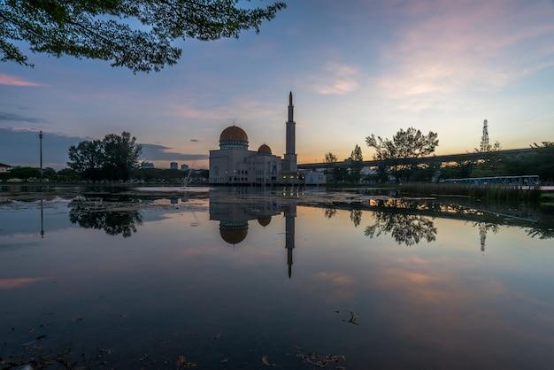 Moskee bij zonsopgang met oever van het meer