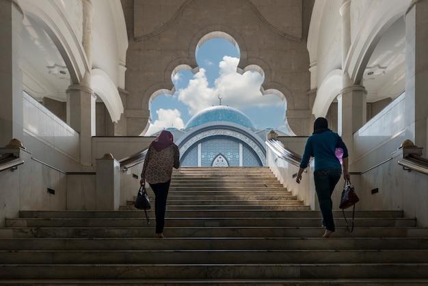 Moskee van maleisië met moslim wowen die bij moskee in aziatisch maleisië lopen ,.