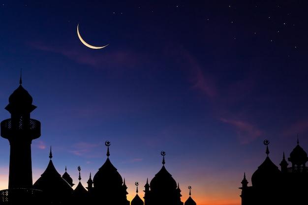 Moskeeën koepel op donkerblauwe schemeringhemel en toenemende maan