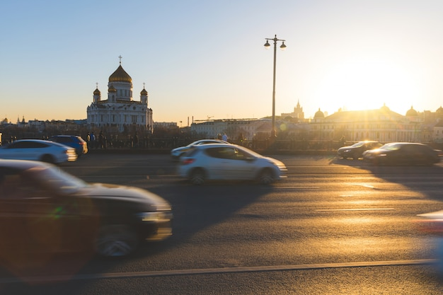 Moskou, kathedraal van christus de verlosser bij zonsondergang met verkeer op de voorgrond