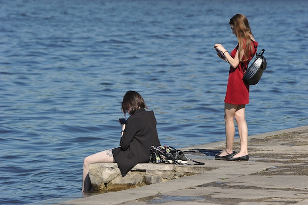 Moskou, rusland - 19 juni 2021: meisjes kijken naar de telefoon aan de oever van de rivier de moskva op een warme zomerdag in moskou