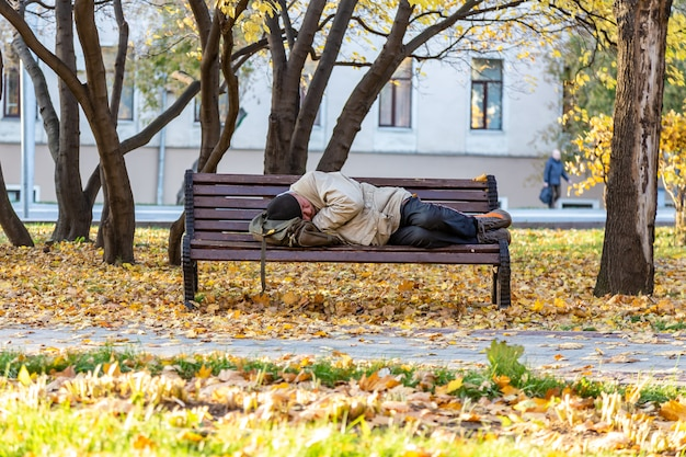 Moskou, rusland: dakloze man slapen op een bankje in het park in het najaar