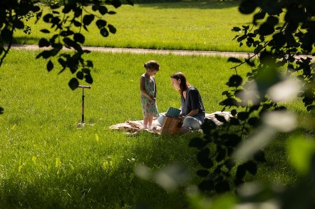 Moskou / rusland - juni 2020: moeder en dochter zitten op het gras en lezen boek