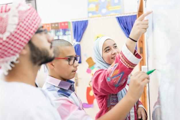 Moslim arabische studenten die een wiskundevraag op het whiteboard oplossen