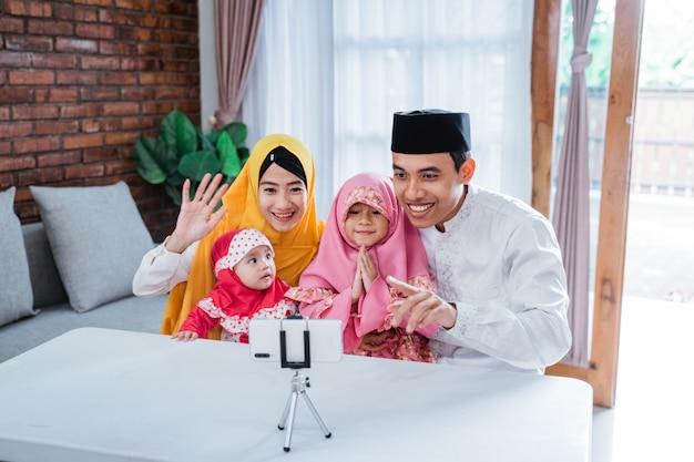 Moslim aziatische familie videobellen met familieleden tijdens eid mubarak met behulp van mobiele telefoon