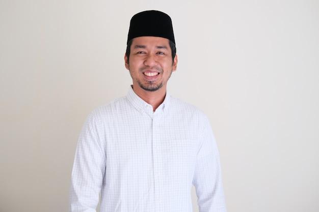 Moslim aziatische man die vriendelijk lacht om iemand te begroeten die op een witte achtergrond wordt geïsoleerd
