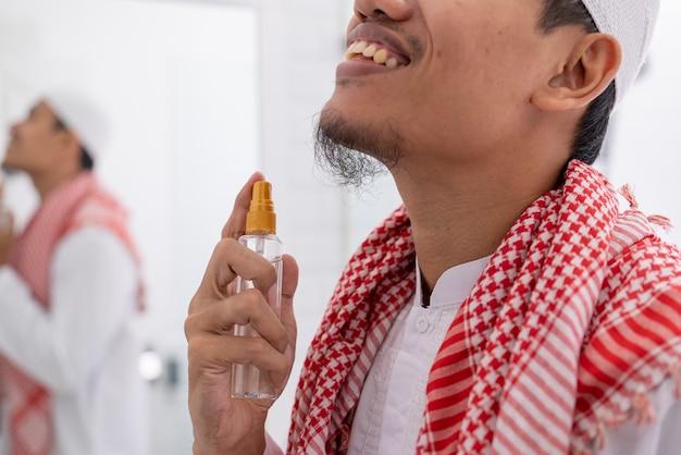 Moslim aziatische man eid mubarak voorbereiden. kleed je aan en breng parfum aan op zijn lichaam