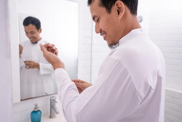 Moslim aziatische man kijkt naar de spiegel en kleedt zich aan voordat hij naar de moskee gaat