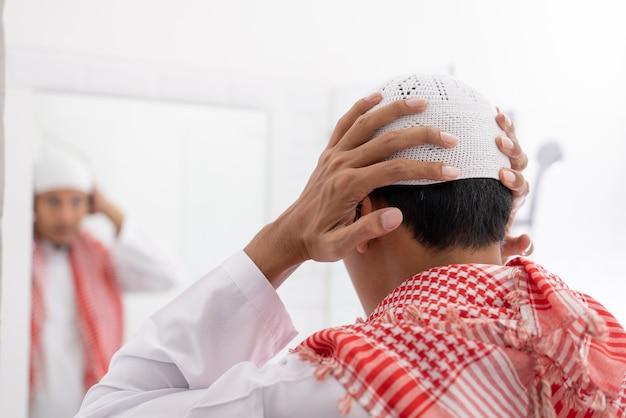 Moslim aziatische man kijkt naar spiegel en kleedt zich aan voordat hij naar de moskee gaat met islamitische hoed of pet op
