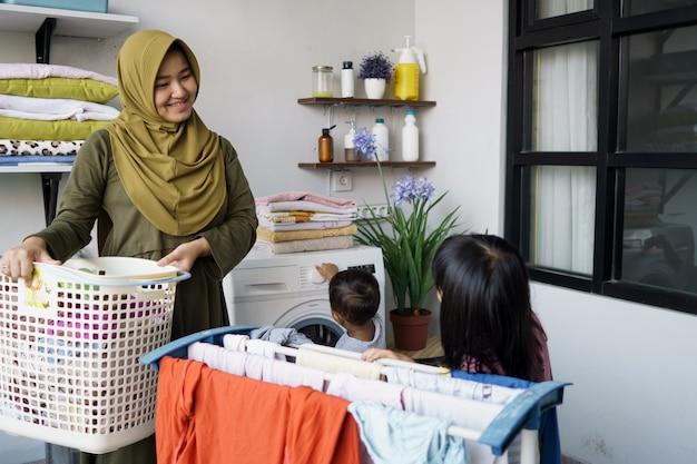 Moslim aziatische moeder en kind meisje kleine helper in wasruimte in de buurt van wasmachine