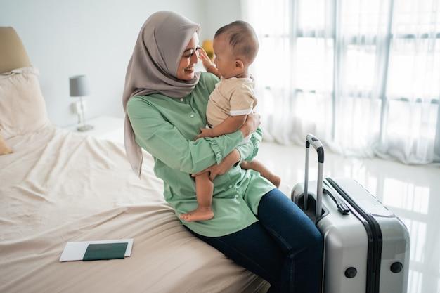 Moslim aziatische moeders dragen hun baby's zittend op het bed