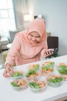 Moslim aziatische vrouw thuis cateringservice lunchdoos voorbereiden afhaalmaaltijden online bestelling