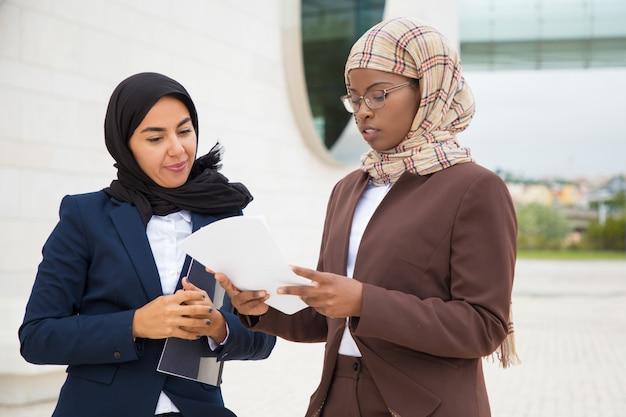 Moslim bedrijfsvrouwen die contracttekst bespreken