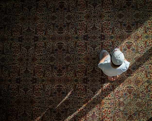 Moslim die in een moskee op traditioneel grondtapijt bidden Premium Foto
