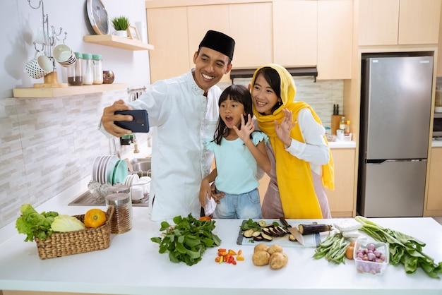 Moslim en gelukkige familie maken van een video, selfie of een telefoontje samen tijdens de voorbereiding van het iftar-diner thuis met dochter