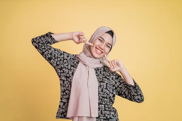 Moslim hijab vrouw twee vingers op de kin en vrolijk lachend