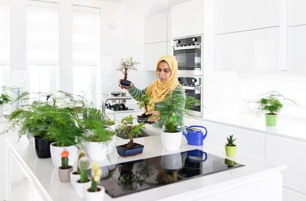 Moslim huisvrouw thuis planten in de keuken water geven