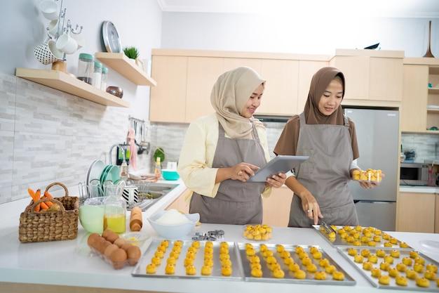 Moslim kleine bedrijfseigenaar die zelfgemaakte nastar-snack maakt om te verkopen. mooie aziatische vrouw met partner die tablet-pc kookt en vasthoudt