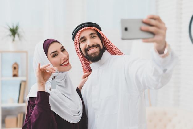 Moslim koppel dream home selfie met huissleutels.