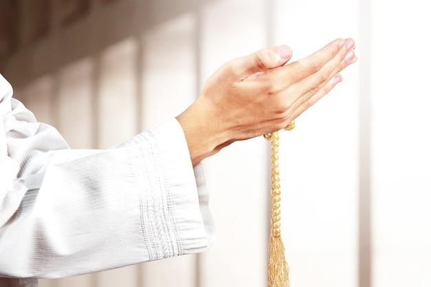 Moslim man bidden met bidparels op zijn handen op de moskee