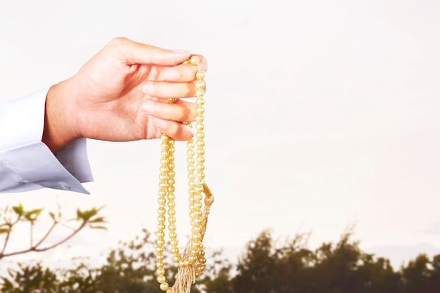 Moslim man bidden met bidparels op zijn handen