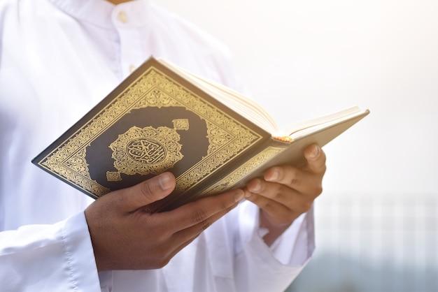 Moslim man die heilige koran leest. islamitisch concept