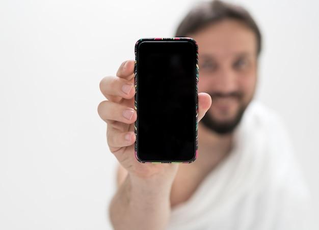 Moslim mannelijke pelgrim met mobiele telefoon
