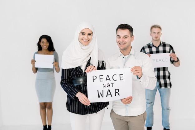 Moslim meisje in witte hijab en blanke man die lacht terwijl ze een poster met een inscriptie vrede geen oorlog