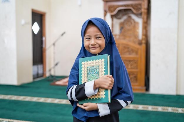 Moslim meisjesjong geitje die koran houden