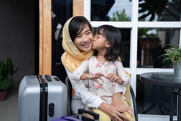 Moslim moeder en dochter met koffer