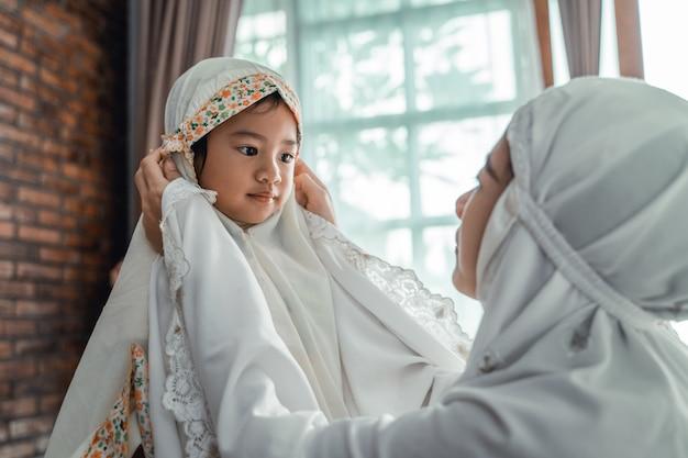 Moslim moeder en kind met sjaal om te bidden