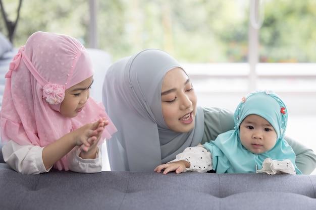 Moslim moeder in hijab is haar dochtertje in de woonkamer, liefdevolle relatie
