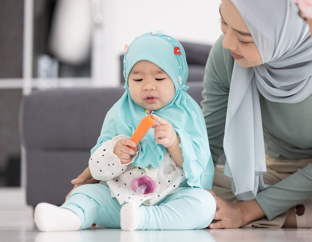 Moslim moeder in hijab is haar dochtertje in de woonkamer, liefdevolle relatie Premium Foto