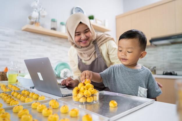 Moslim moeder kijkt naar laptop terwijl ze cake maakt met haar zoon in de keuken