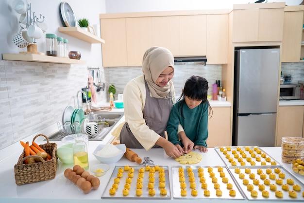 Moslim moeder tijdens ramadan activiteit met haar dochter die samen een nastar cake maakt