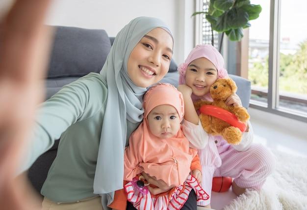 Moslim moeder toekomstig moederschap in hijab en zelfportret nemen in de woonkamer