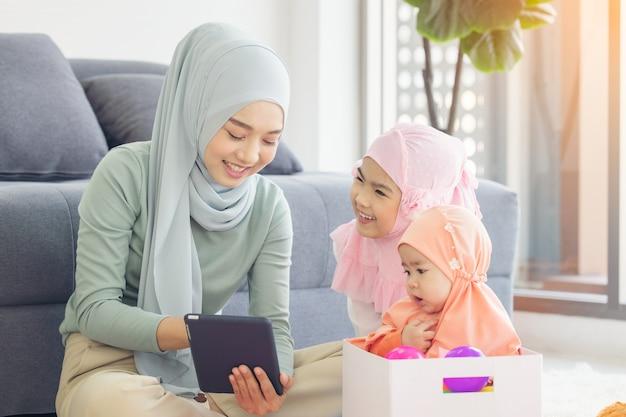 Moslim moeder werken met laptop en schattige kleine baby speelspeelgoed in de huiskamer.
