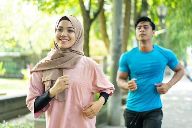 Moslim paar joggen samen wanneer buiten oefenen in het park