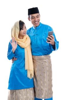 Moslim paar met behulp van mobiele telefoon geïsoleerd op witte achtergrond