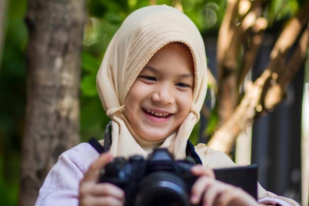 Moslim schoolkind. mooi klein meisje in hijab met behulp van digitale camera.